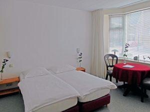 Illustratie: foto van de bedden en de tafel in de erker van de kamer A.J.M. Steentjes van het bed and breakfast van Hoek van Holland.